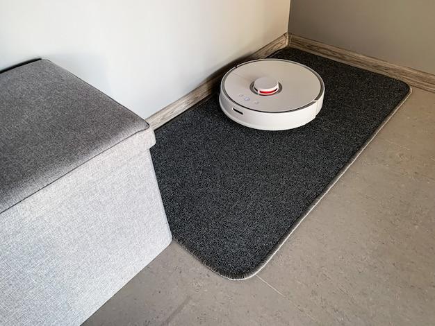 Maison intelligente. robot aspirateur tourne sur le sol dans un salon.