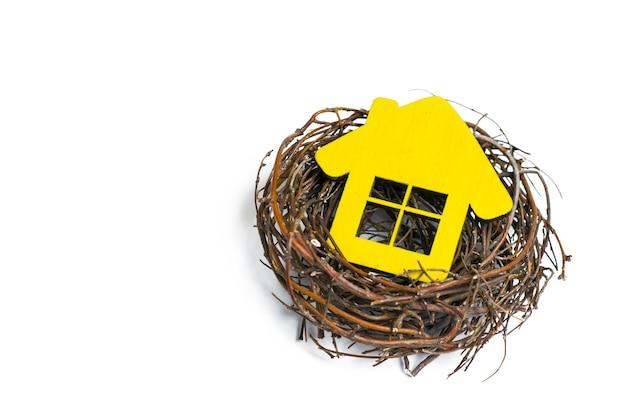Maison jaune dans le nid sur blanc isolé