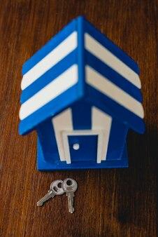 Maison de jouet en bois avec des motifs de plage et maritimes et des clés de la maison.