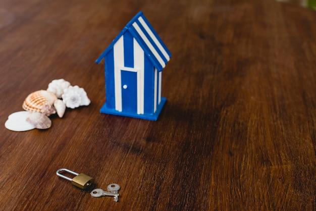 Maison de jouet en bois avec des motifs de plage et maritimes et quelques clés de maison.