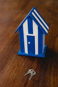 Maison de jouet en bois avec motifs de plage et maritimes et quelques clés de la maison.