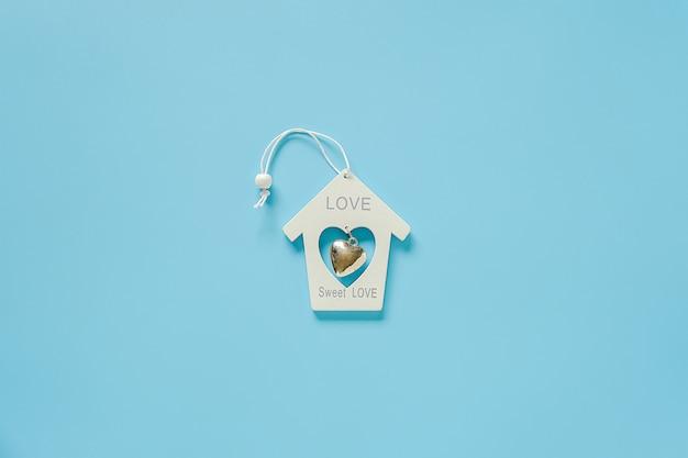 Maison de jouet de décoration en bois blanc avec coeur en métal sur fond bleu