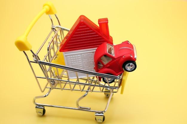 Une maison de jouet et une petite voiture rouge dans un petit panier. achat majeur.