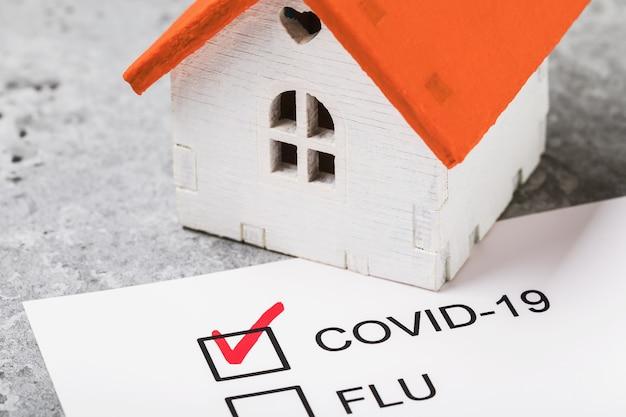 Maison de jouet sur la table et forme avec le résultat confirmé sur le traitement à domicile contre le coronavirus