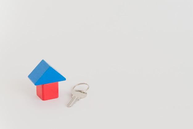 Maison de jouet et véritable clé en métal sur l'espace blanc