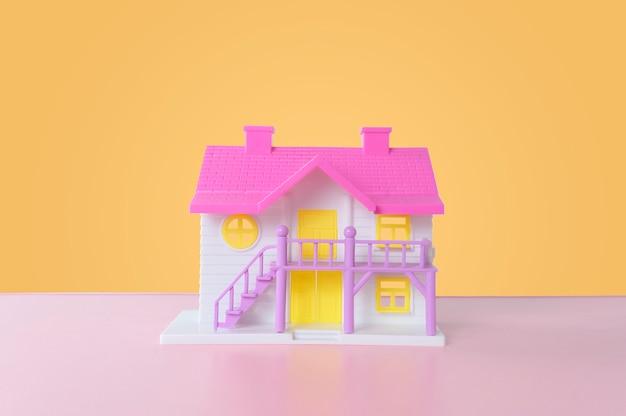 Maison de jouets colorés sur mur jaune. propriété immobilière conceptuelle.
