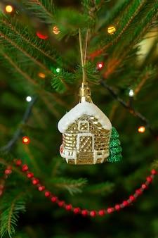 Une maison de jouets est accrochée à une branche d'un arbre de noël