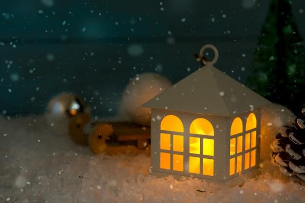 La maison de jouets de noël est enveloppée dans le fond enneigé d'un vrai sapin dans la neige, tonique.