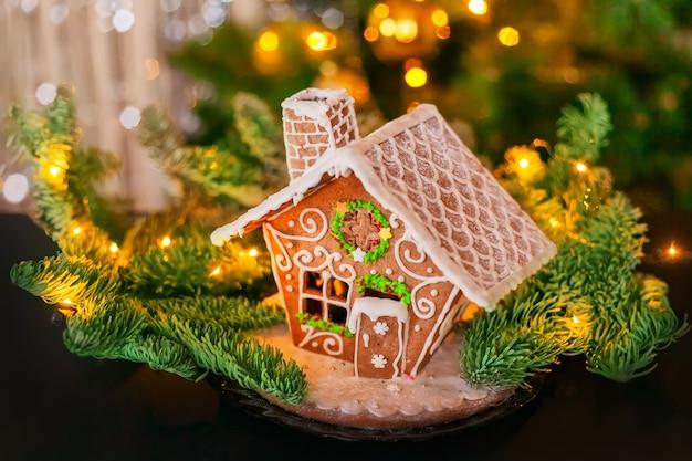 Une maison magique en pain d'épice faite maison avec des branches de pin et des lumières dorées et argentées en arrière-plan. joyeux noël et bonne année voeux et carte postale