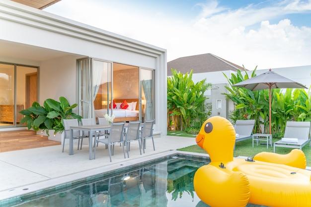 Maison ou maison design extérieur montrant une villa avec piscine tropicale avec jardin de verdure, solarium, parasol, serviettes de piscine et canard flottant