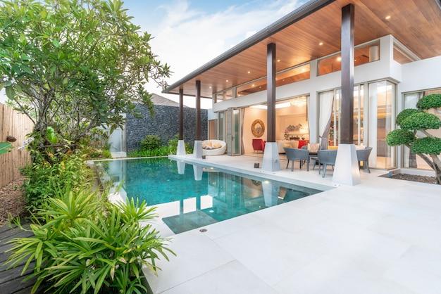 Maison ou maison design extérieur montrant une villa de piscine tropicale avec jardin de verdure,