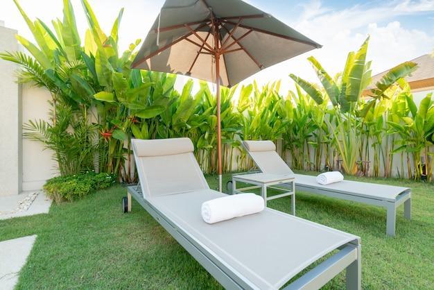 Maison ou maison design extérieur montrant une villa de piscine tropicale avec lit de bronzage, parasol