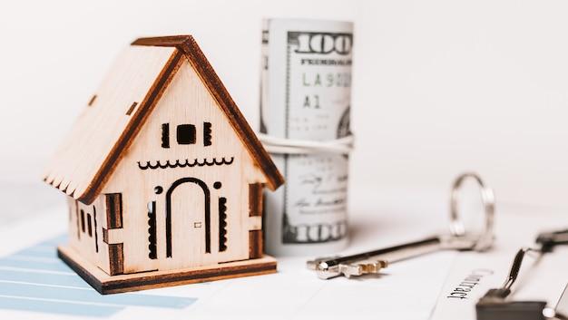 Maison miniature et argent sur documents. investissement, immobilier, maison, logement