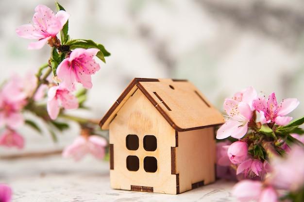 Maison miniature, branche fleurie au printemps.