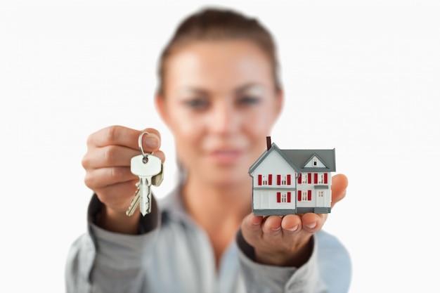 Maison miniature et clés présentées par une femme agent immobilier