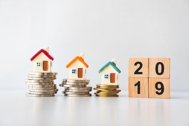 Maison miniature sur des pièces de monnaie avec année de bloc en bois 2019 en tant que concept d'entreprise et de propriété