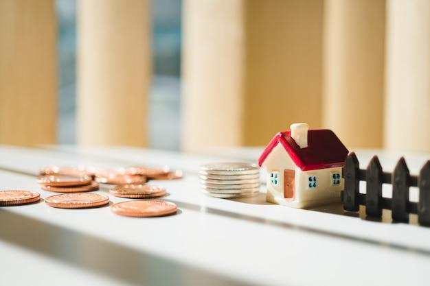 Maison miniature sur des pièces de pile en utilisant comme propriété et concept financier