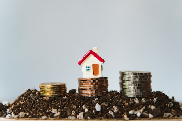 Maison miniature avec pile pièces sur tas de terre