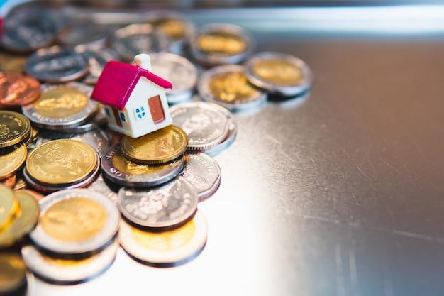 Maison miniature sur des piles de pièces de monnaie en tant que propriété immobilière et concept financier