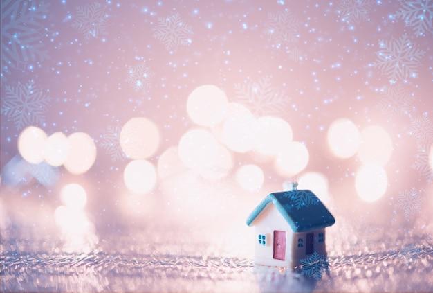 Maison miniature avec toit bleu sur décoration floue de noël