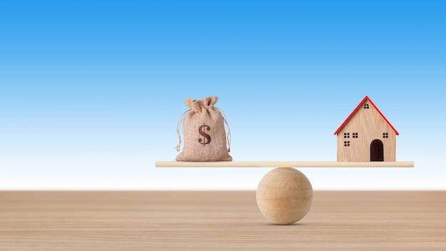 Maison modèle sur balançoire en bois en équilibre avec sac d'argent sur fond bleu.