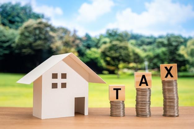 Une maison modèle blanche et un cube en bois sur une pièce de monnaie avec des lettres taxes.