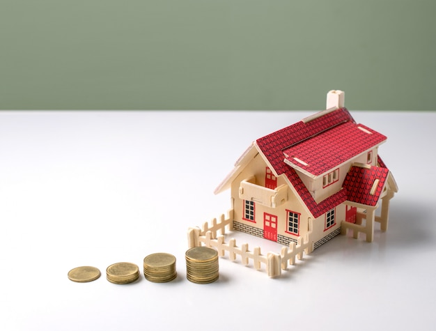 Maison modèle en bois avec de l'argent sur une table blanche avec espace de copie prêt