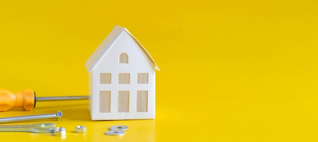 Maison modèle avec clé en métal et instrument sur fond jaune pour la rénovation domiciliaire