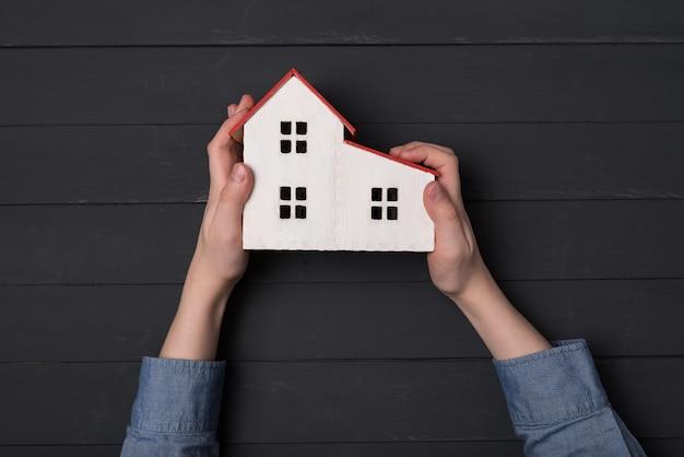 Maison modèle dans les mains des enfants, sur fond noir. concept de maison propre. vue de dessus.