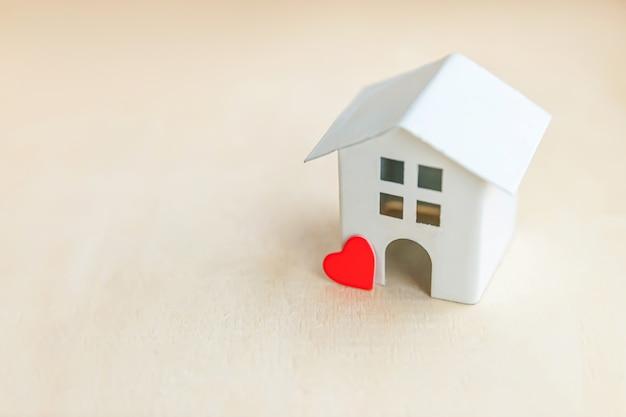 Maison modèle jouet avec coeur rouge sur fond en bois. village écologique, fond environnemental abstrait