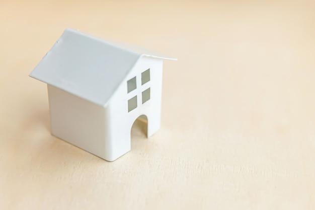 Maison modèle jouet miniature sur fond de bois. village écologique, fond environnemental abstrait