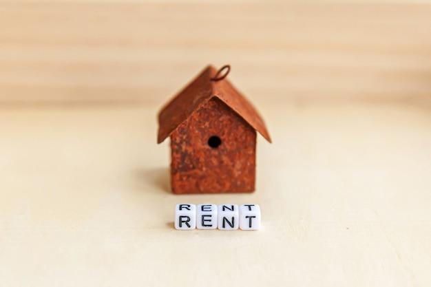 Maison modèle jouet miniature avec inscription mot lettres louer sur fond de bois
