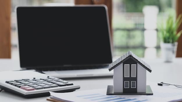 La maison modèle met un document graphique avec une calculatrice et un ordinateur portable, concept d'entreprise immobilière, commerce de la maison.