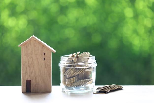 Maison modèle avec pile de pièces d'argent sur fond vert naturel