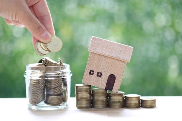Maison modèle sur pile de pièces d'argent et main de femme mettant une pièce dans la bouteille en verre sur fond vert naturel, investissement commercial et concept immobilier
