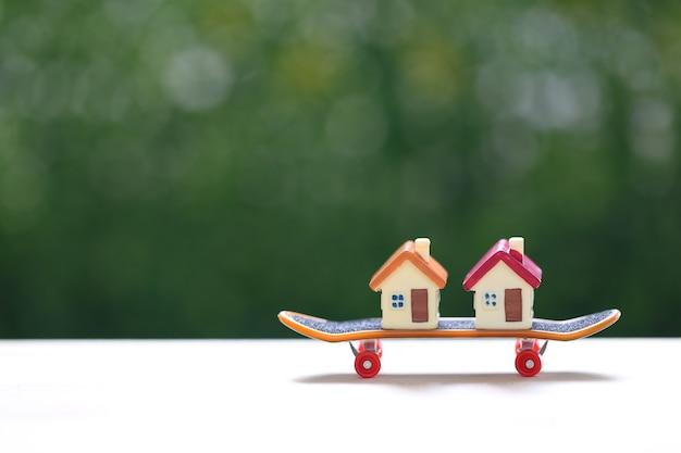 Maison modèle sur planche à roulettes avec fond vert naturel, investissement commercial et concept immobilier