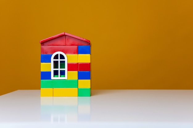 Maison multicolore en plastique faite de pièces design sur une table blanche et un mur jaune vif