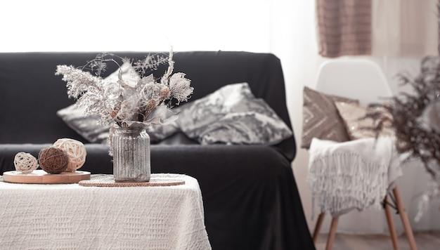 Maison de nature morte chaleureuse avec un canapé noir et une décoration dans le salon.