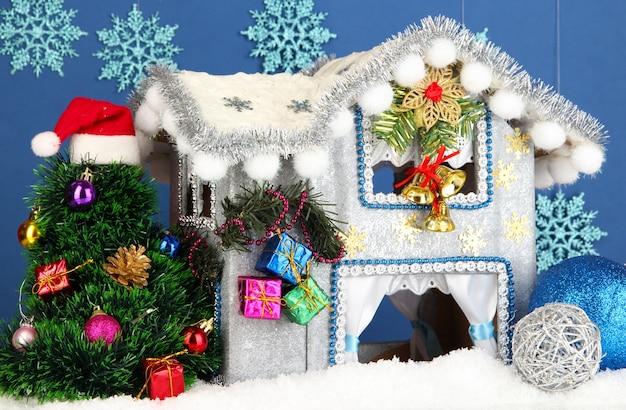 Maison de noël décorée sur fond bleu