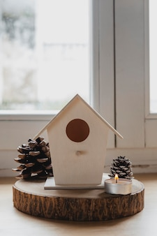 Maison d'oiseau vue de face avec des pommes de pin et des bougies