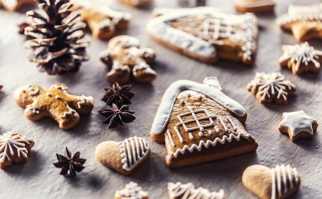 Maison avec pain d'épice et autres biscuits de noël accompagnés de cannelle et de pommes de pin.
