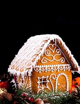 Maison de pain d'épice avec des décorations de noël sur un backgrond noir