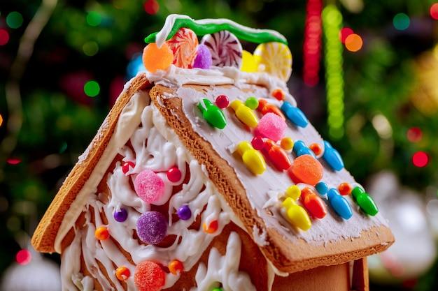 Maison en pain d'épice décorée avec des bonbons sur la surface de l'arbre de noël