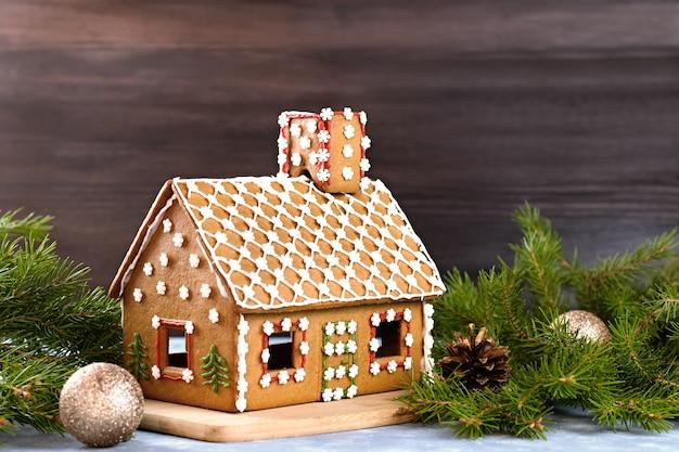 Maison en pain d'épice décorée en gros plan avec des décorations en pin et des boules dorées. bokeh doré en arrière-plan