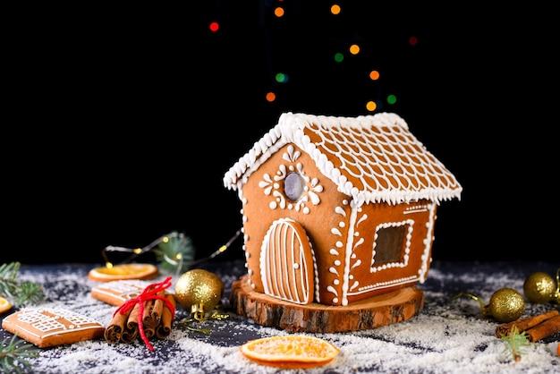 Maison de pain d'épice d'hiver avec la lumière des fenêtres
