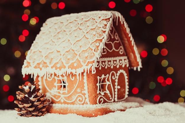 Maison en pain d'épice sur des lumières défocalisées de sapin décoré de chrismtas
