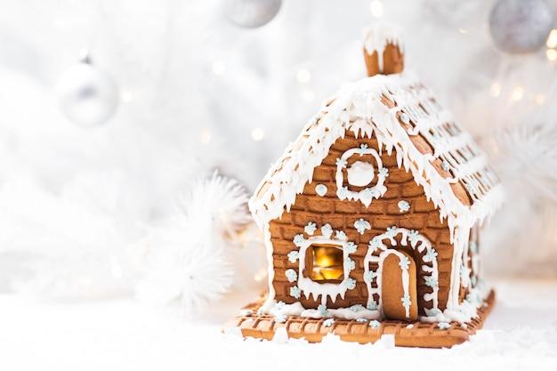 Maison en pain d'épice maison, sapin de noël blanc et guirlande lumineuse