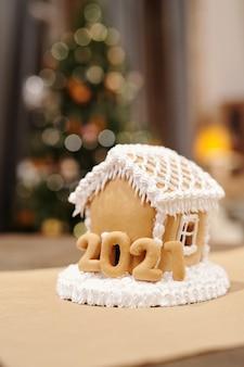 Maison de pain d'épice maison savoureuse décorée de crème fouettée debout sur la table