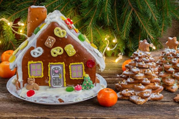 Maison en pain d'épice avec des mandarines et des lumières de noël sur table en bois