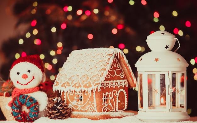 Maison de pain d'épice sur la neige, bonhomme de neige et chandelier